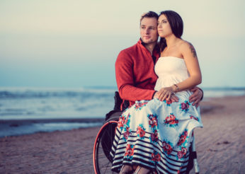 Handicapped young couple resting on a beach.