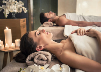 Young man and woman lying down on massage beds at Asian luxury spa and wellness center
